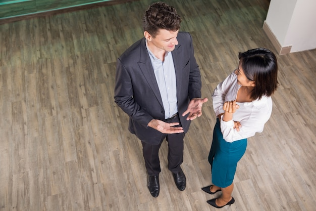 Content business man and woman talking in hall