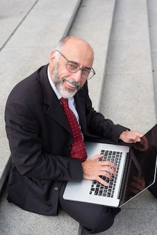 Content businessman in eyeglasses using laptop on street