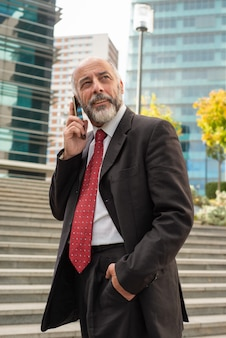 Content businessman talking by smartphone and looking away