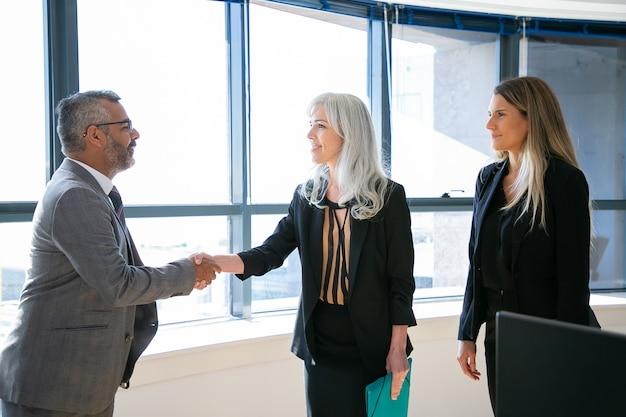 콘텐츠 기업인 인사, 회의 및 미소. 회색 머리 사업가와 안경 핸드 셰이 킹, 이야기하고 그녀를보고있는 성공적인 인도 ceo. 비즈니스 및 파트너십 개념