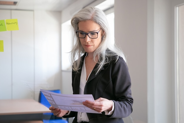 Content businesswoman in eyeglasses reading statistics. successful concentrated grey-haired employer in suit standing in office room and holding document. marketing, business and management concept