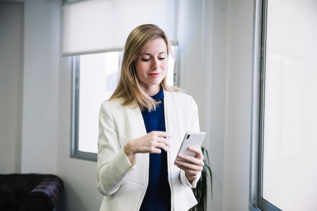 Content businesswoman looking at smarphone
