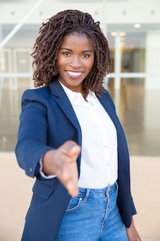 Content businesswoman reaching hand for handshake