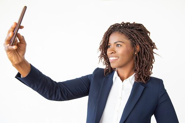 Donna di affari contenta che prende selfie con lo smartphone