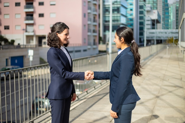 Content businesswomen shaking hands