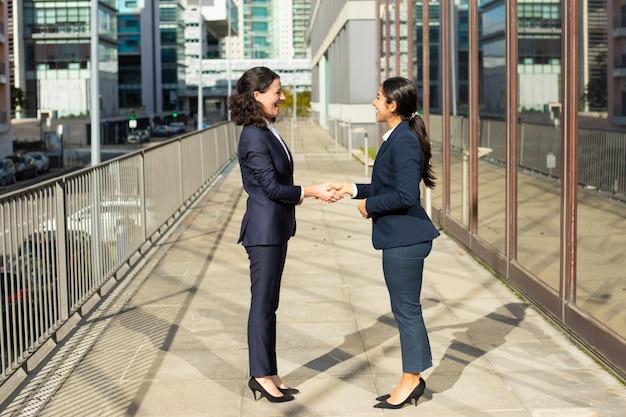 Довольные деловые женщины разговаривают на улице