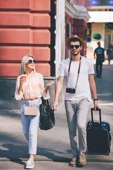 Довольная случайная пара туристов, гуляющих по городу. семейный туризм. летний отпуск. получение новых впечатлений и концепция осмотра достопримечательностей