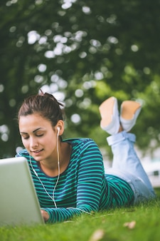 Content casual student lying on grass using laptop