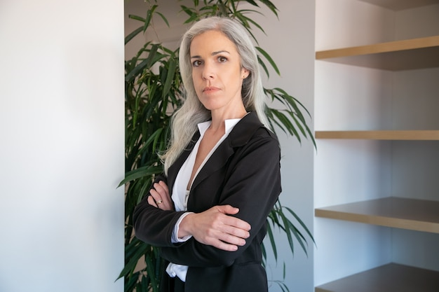 Content caucasian businesswoman standing with folded hands. portrait of confident adult beautiful female office employer in black blouse posing at work. business, company and management concept