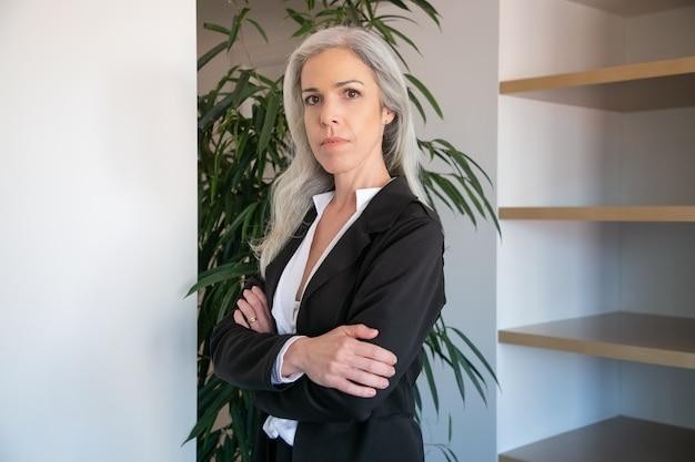 콘텐츠 접힌 손으로 서 백인 사업가입니다. 직장에서 포즈 검은 블라우스에 자신감이 성인 아름다운 여성 사무실 고용주의 초상화. 비즈니스, 회사 및 관리 개념