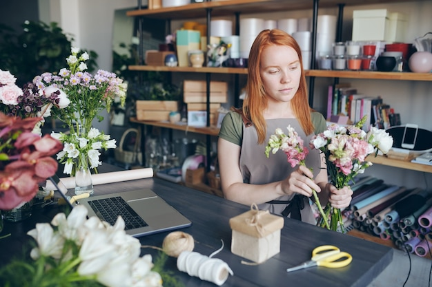 Content concentrated young redhead woman in apron standing between counter and shelves and creating beautiful floral arrangement in flower workshop