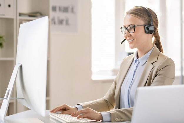 Content confident attractive young call center operator in headset with microphone sitting at table and typing on computer while answering call