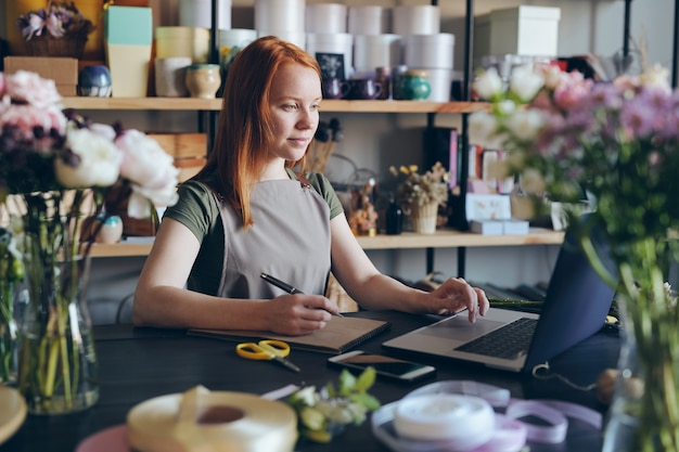 Content confident attractive young woman in apron standing at counter and using laptop while processing online orders in flower shop