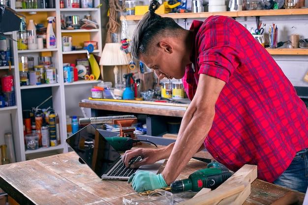 Довольный уверенный красивый молодой работник в общем носить пояс с инструментами, стоящий в мастерской