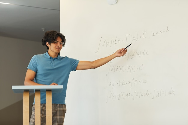 Content confident mixed race student boy pointing at whiteboard while explaining math solution at university class