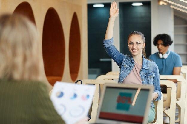 Довольная уверенная умная девушка в очках поднимает руку, чтобы попросить учителя в классе в бизнес-школе