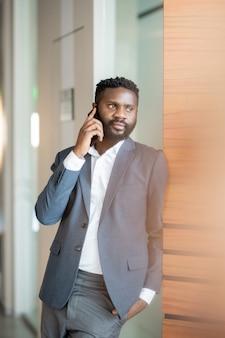 Довольный уверенный молодой черный бизнесмен в куртке, стоящей у стены и разговаривающей по мобильному телефону
