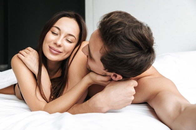 Content couple man and woman hugging together, while lying in bed at home or hotel apartment
