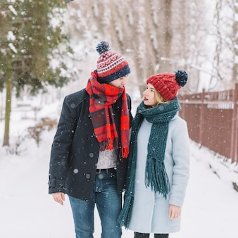 Content couple walking in snowfall