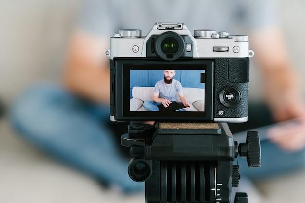 ソーシャルメディア向けのコンテンツ作成。ひげを生やした男性がカメラの画面で自分のビデオを撮影している画像。現代の技術とブログ機器のコンセプト。