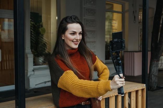 Создатель контента, блоггер, влогер, молодая женщина, делающая селфи, снимая себя и развлекаясь в городе