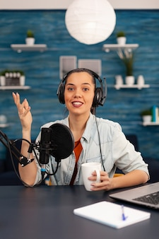 Content creator looking at camera while talking into microphone during beauty podcast. creative online show on-air production internet broadcast host streaming live video, recording digital social
