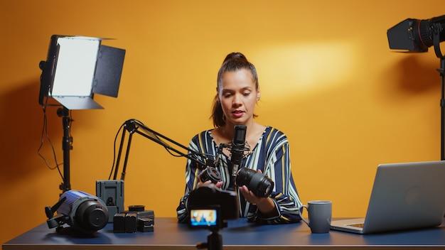 전문 스튜디오 세트에서 카메라 렌즈를 비교하는 콘텐츠 제작자입니다. 온라인 인터넷 웹 쇼를 위한 비디오 사진 장비를 말하는 소셜 미디어의 콘텐츠 제작자 뉴 미디어 스타 인플루언서