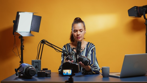 Content creator making a camera lens comparison in her professional studio set. content creator new media star influencer on social media talking video photo equipment for online internet web show