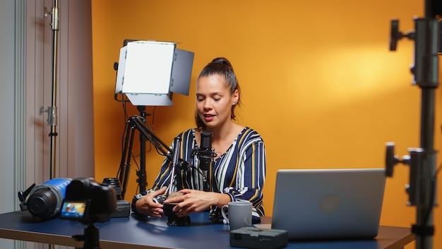 콘텐츠 제작자는 전문 스튜디오에서 카메라를 향해 플루이드 헤드를 검토하고 있습니다. 웹 가입자 및 배포, 디지타를 위한 비디오 장비에 대한 온라인 인터넷 콘텐츠를 만드는 소셜 미디어 인플루언서