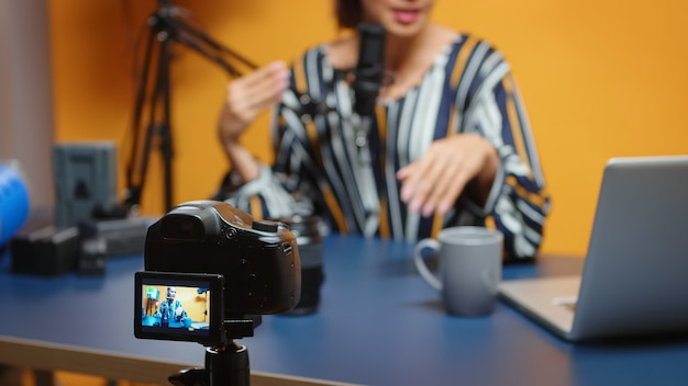 Content creator talking about camera lens in new podcast episode, selective focus on recording camera. new media star influencer on social media talking video photo equipment for online internet web s