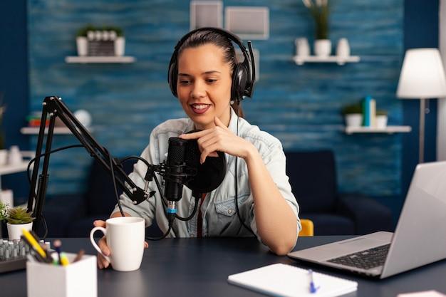 ヘッドフォンを装着したコンテンツクリエーターが、視聴者向けに新しいポッドキャストシリーズを作成しています。プロの機器を使用してスタジオでオンライントークショーを話し、録音するvloggerの女性