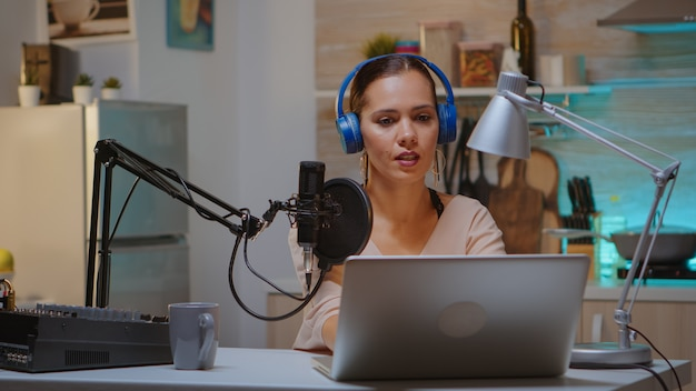 ポッドキャストの新しいエピソードを録画しながらヘッドホンを装着しているコンテンツ作成者。クリエイティブオンラインショープレゼンターオンエアオンライン制作インターネット放送ショーホストストリーミングライブコンテンツ、レコーディングメディア