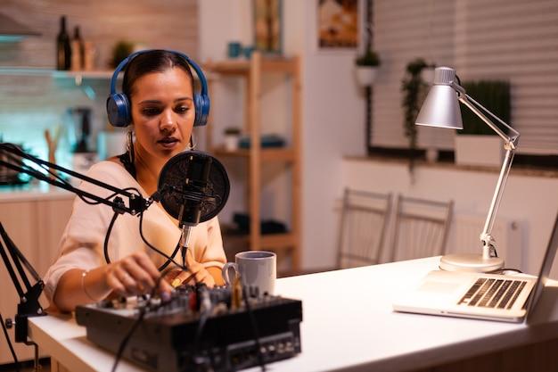 팟캐스트용 새 에피소드를 녹음하는 동안 헤드폰을 끼고 있는 콘텐츠 제작자