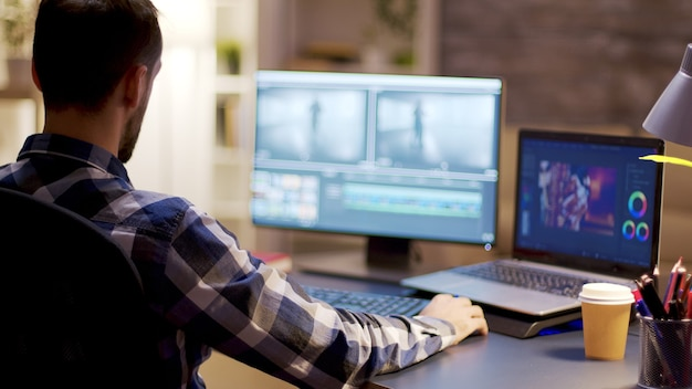 Content creator working on post production for a multimedia project in home office.