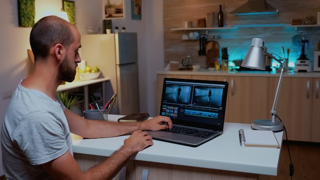 夜間に自宅からラップトップでリモート作業するコンテンツ作成者。真夜中にモダンなキッチンの机の上に座っているプロのラップトップでオーディオフィルムモンタージュを編集するビデオグラファー