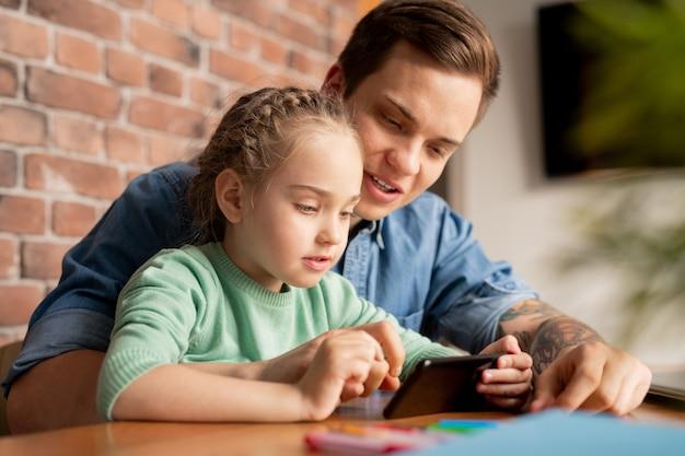 Довольная любопытная дочь с заплетенными волосами сидит за столом и играет в видеоигру по телефону, пока ее отец объясняет, как пройти уровень