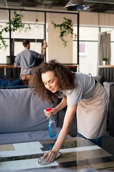 카페의 표면을 소독하는 동안 천으로 커피 테이블을 닦는 앞치마에 콘텐츠 곱슬 머리 소녀