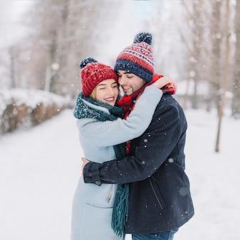 Contenuto che abbraccia coppia in nevicata