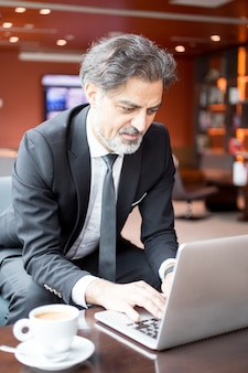 Content entrepreneur working on laptop in lobby