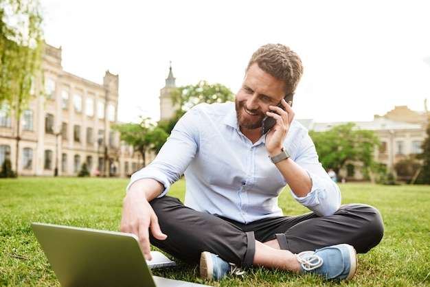 Content european man in business clothing, sitting on grass in park with legs crossed and talking on cell phone while using silver laptop