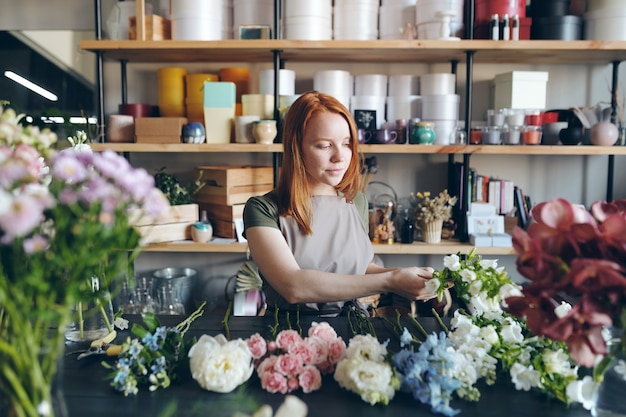 Content experienced young woman in apron standing at desk and choosing fresh flowers for bouquet in flower shop