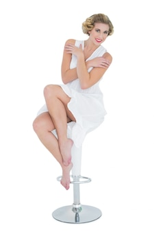 Content fashion blonde model posing sitting on bar chair