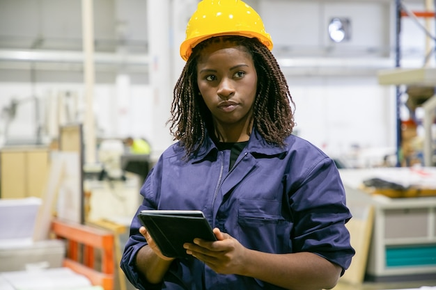 Content female plant worker standing with tablet and looking away