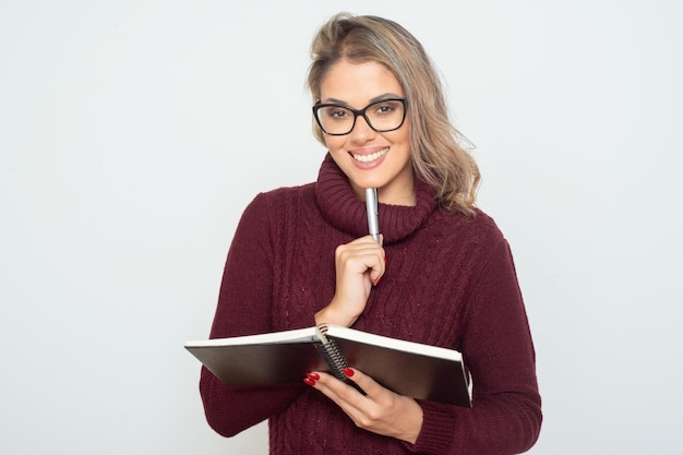 Content female student holding notebook and pen