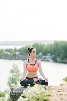 Content female yogis in sports bra sitting in lotus position and contemplating nature while enjoying meditation outdoors