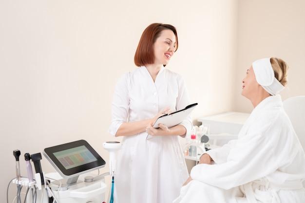 化粧品の手順の準備をしながらバスローブで成熟したクライアントと話しているフォルダを持つコンテンツフレンドリーな赤毛の美容師