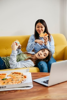 Content girls watching laptop and eating pizza
