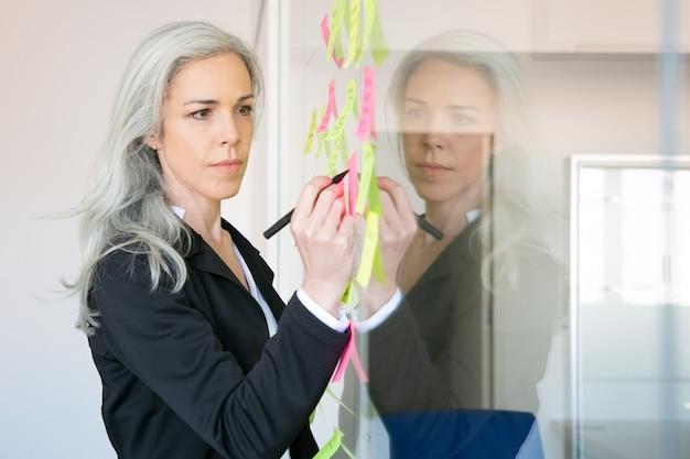 Donna di affari caucasica dai capelli grigi contenuto che scrive sull'adesivo con l'indicatore. responsabile femminile professionale concentrato che condivide l'idea per il progetto e che prende nota.