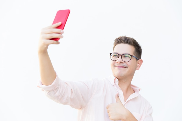 Content guy in eyeglasses making like gesture and taking selfie