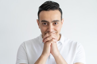 Content handsome man hoping for luck and holding hands together near mouth.